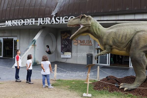 Tres niños miran con interés una reproducción de dinosaurio a la entrada del Museo del Jurásico de Asturias. Colunga. Asturias. España © Javier Prieto Gallego