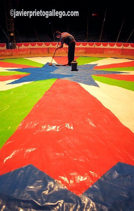 Un mozo limpia la pista del Circo Mundial.
