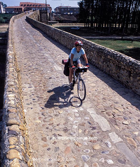 Una peregrina pasa en bicicleta sobre el puente medieval de Hospital de Órbigo. Camino de Santiago Francés. León. Castilla y León. España. © Javier Prieto Gallego