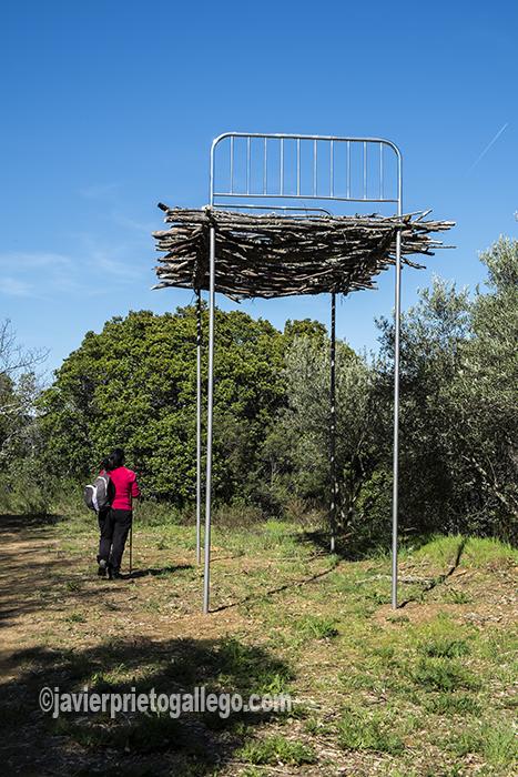 Una senderista pasa junto a una obra de Alfredo Omaña ubicada en el Camino de los Prodigios. Sierra de Francia. Salamanca. España ©Javier Prieto Gallego