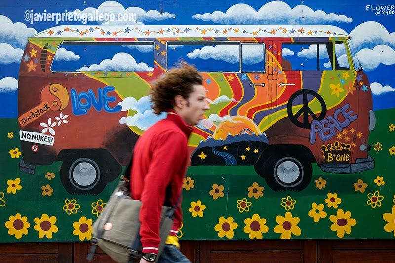 Un joven pasa ante un dibujo que decora un puesto de flores en Amsterdam. Holanda. © Javier Prieto Gallego .