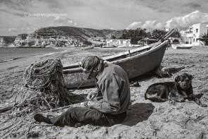 Un pescador repara sus redes sobre la arena de la playa de Agua Amarga. Cabo de Gata. Almería. España, marzo de 1999 © Javier Prieto Gallego