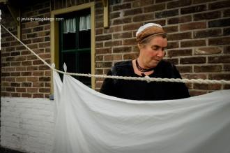 Una mujer lava a mano y tiende la ropa en el barrio de pescadores del museo al aire libre de Zuiderzee Museum, en Enkhuizen, en la región de Noord Holland, Holanda, 2005 © Javier Prieto Gallego