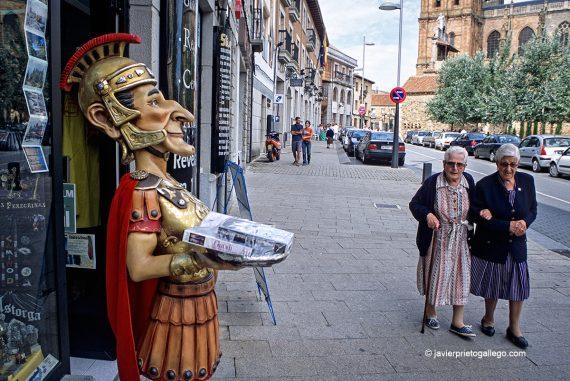 Dos mujeres pasan ante el reclamo publicitario de una tienda de recuerdos en Astorga. Camino de Santiago Francés. León. Castilla y León. España. © Javier Prieto Gallego