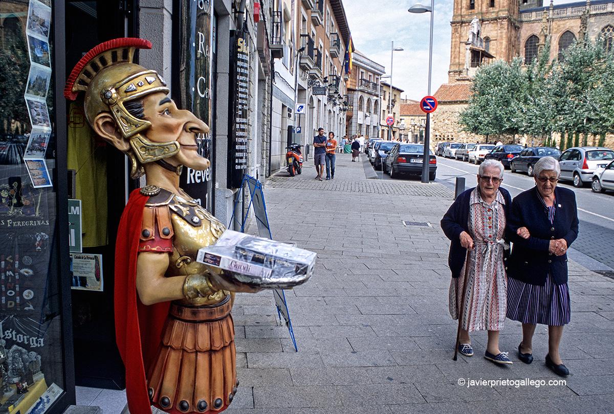 Dos mujeres pasan ante el reclamo publicitario de una tienda de recuerdos en Astorga. Camino de Santiago Francés. León. Castilla y León. España. Javier Prieto Gallego